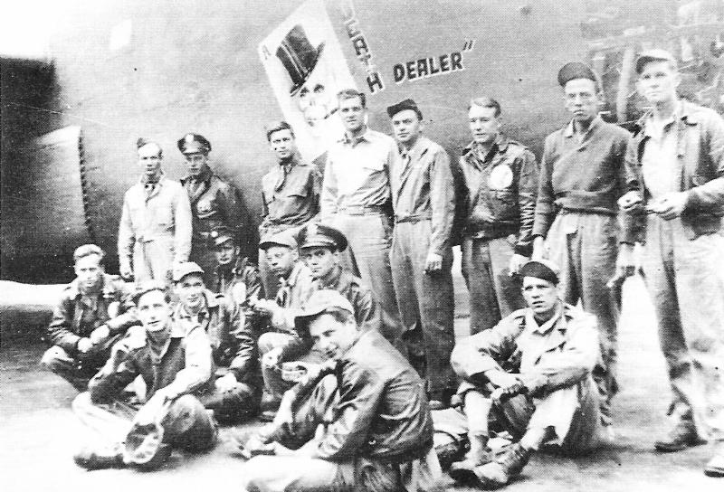 """Die Besatzung der """"Death Dealer"""" in ihrem Wüstencamp. In der Mitte steht rechts neben dem aufgemalten Totenkopf der Pilot Alva Jack Geron. (124_2)"""