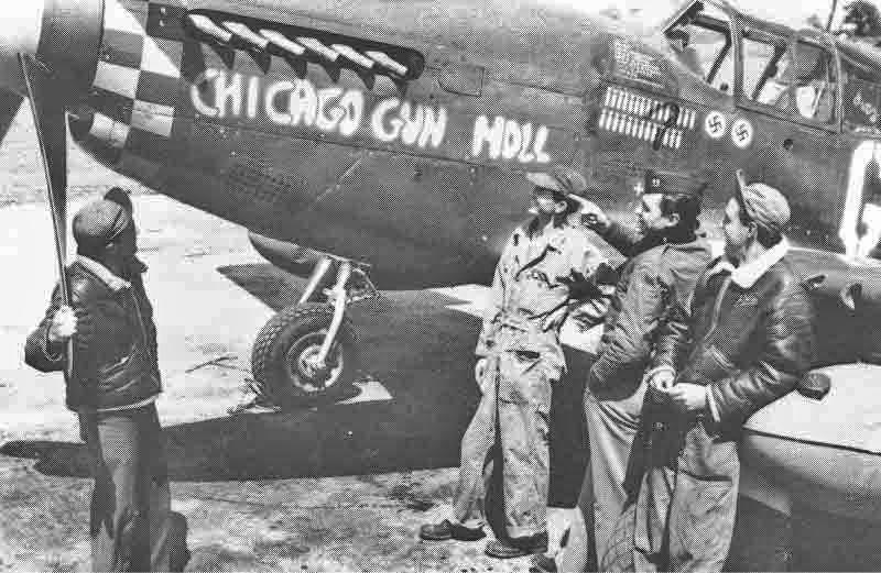 """Die einzige bekannte Aufnahme der """"Chicago Gun Moll"""" zeigt Captain Brown inmitten seiner Flugzeugwarte. Brown hatte zu jenem Zeitpunkt zwei deutsche Flugzeuge abgeschossen, wie an den beiden Hakenkreuzen unter dem Cockpit zu erkennen ist. (369_1)"""